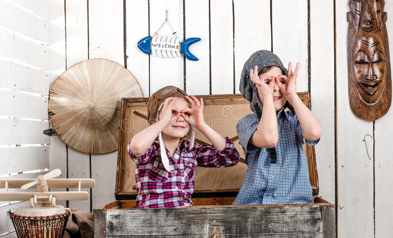 Two little kids in pilot hats making glasses with hands royalty free stock images