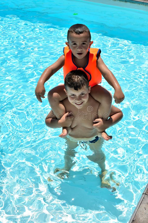 Happy kids in the swimming pool stock photo