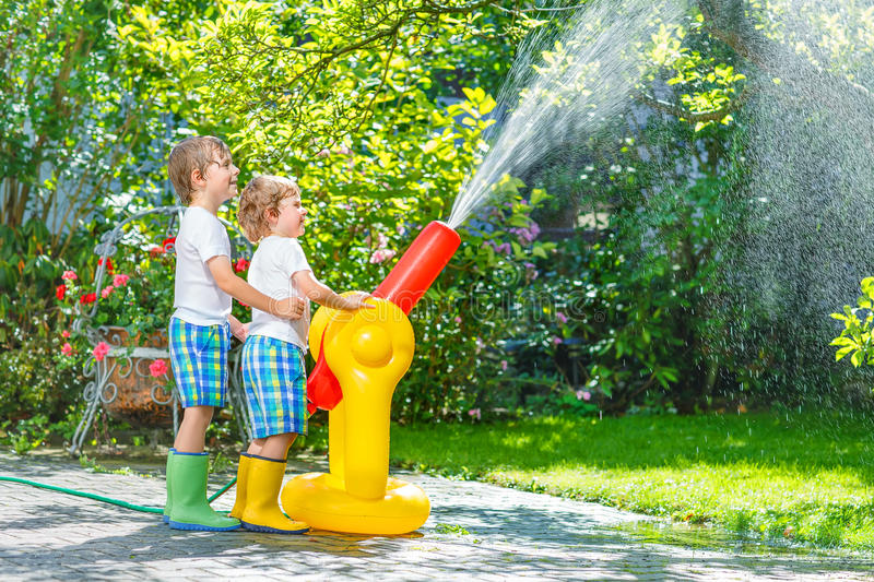 Two little kids playing with garden hose and water in summer. Two funny little brother boys playing together and splashing with a garden hose on hot and sunny stock photo