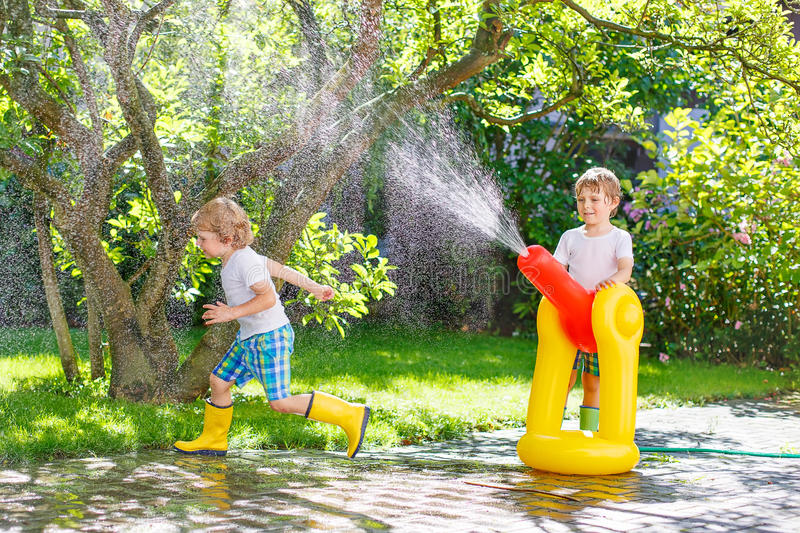 Two little kids playing with garden hose and water in summer. Two funny little friends playing together and splashing with a garden hose on hot and sunny summer stock image