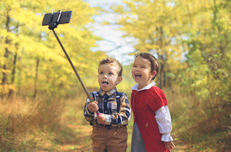 two little kids taking selfie in the park royalty free stock images