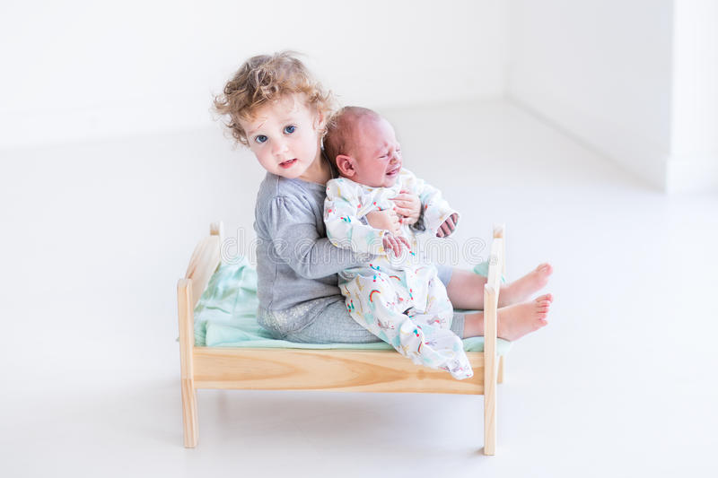 Two little kids in a wood toy bed. Cute toddler girl playing with her newborn baby brother in a wood toy bed stock image