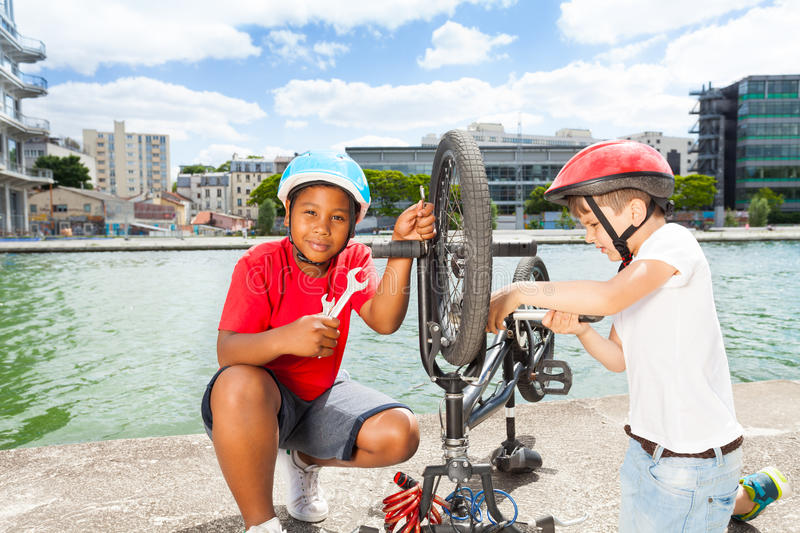 Two little mechanics repairing bike outdoors stock photo
