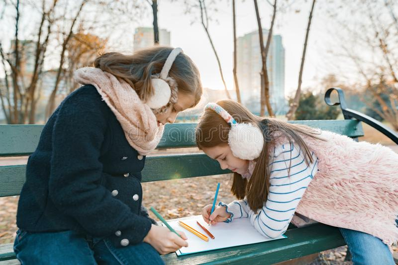 Two little pretty artists drawing with colored pencils, girls sitting on a bench in sunny autumn park, golden hour royalty free stock image