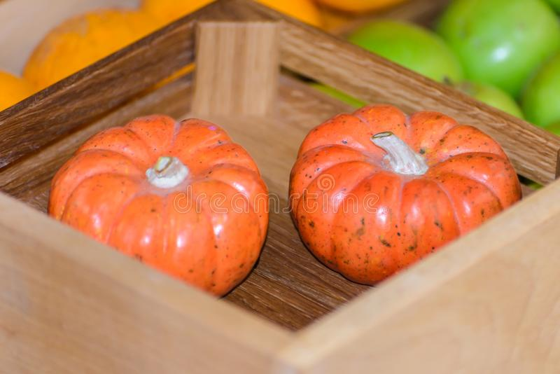 Two little pumpkins in a box among vegetables royalty free stock photography