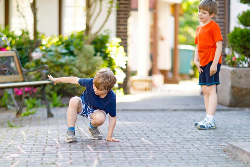 Two little school and preschool kids boys playing hopscotch on playground. Outdoors together. children having fun with outdoor activities in summer on sunny day stock photography