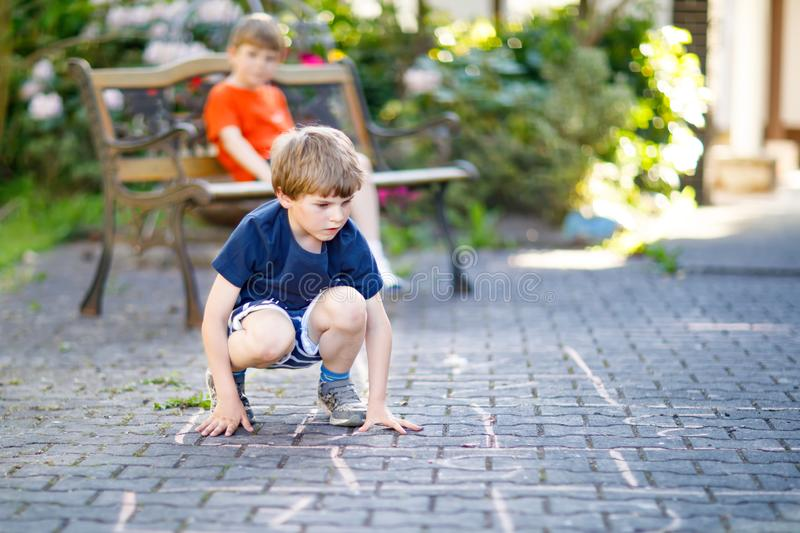 Two little school and preschool kids boys playing hopscotch on playground. Outdoors together. children having fun with outdoor activities in summer on sunny day stock photos