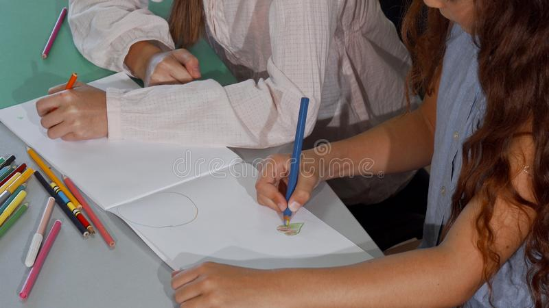 Two little schoolgirls coloring together during art class royalty free stock image