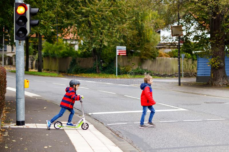 Two little schoolkids boys running and driving on scooter on autumn day. Happy children in colorful clothes and city stock photography