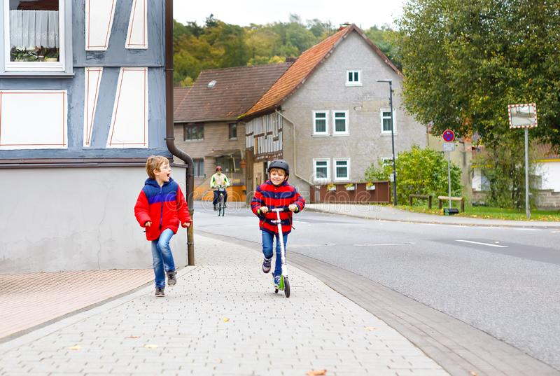 Two little schoolkids boys running and driving on scooter on autumn day. Happy children in colorful clothes and city royalty free stock images