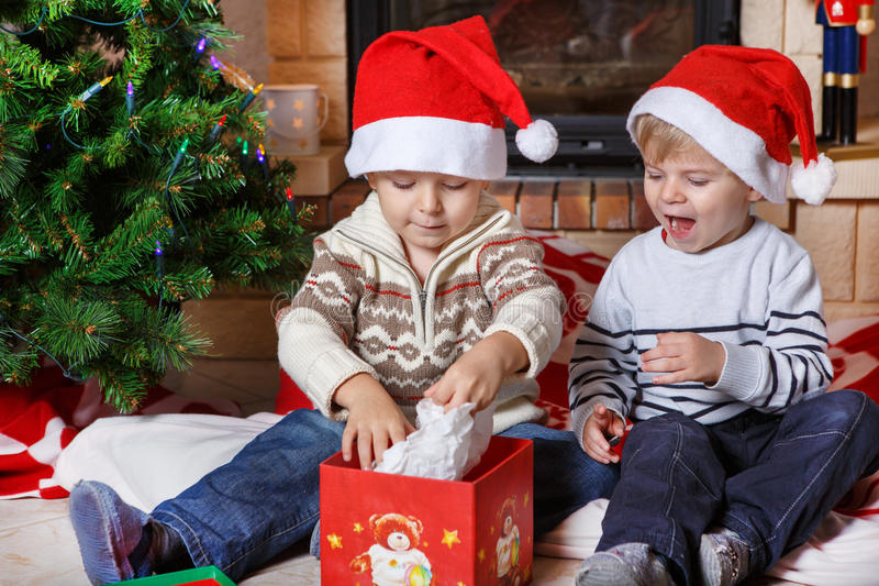 Two little sibling boys being happy about christmas present stock photos