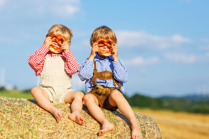 Two little sibling boys and friends sitting on hay stack and ea royalty free stock photos