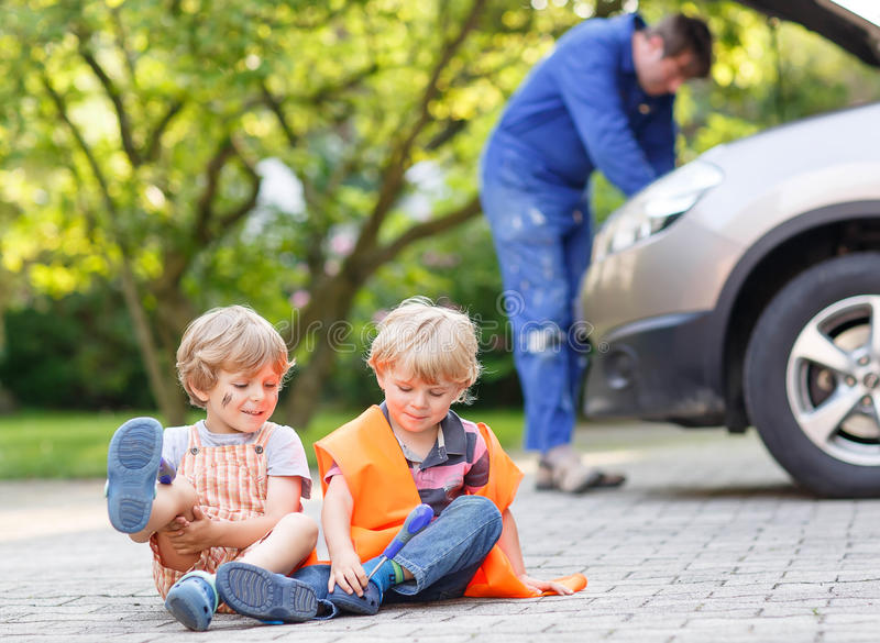 Two little sibling boys in orange safety vest during their father repairing family car. Two little friends in orange safety vest during their father repairing stock images