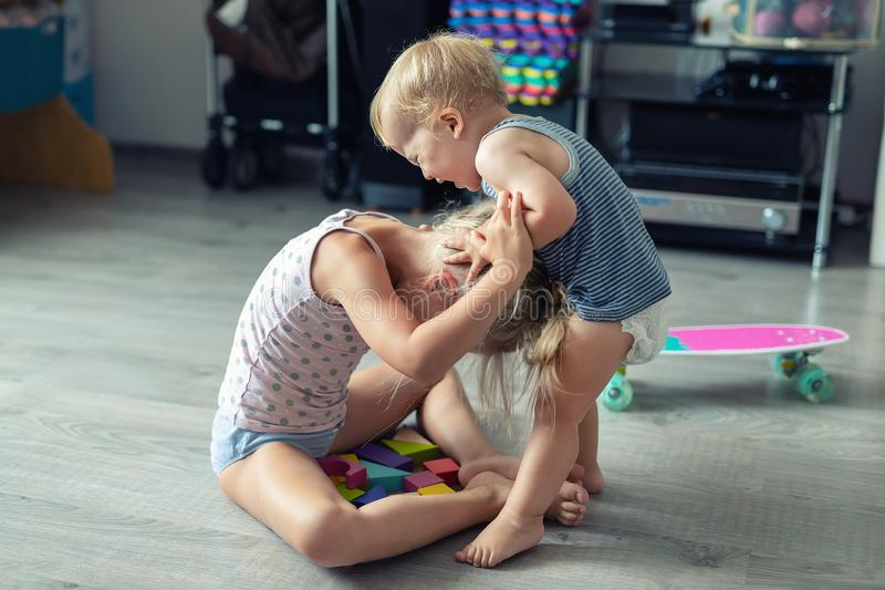 Two little siblings children quarrelling after playing at room at house. Crying offended toddler boy arguing with elder sister. Family rivalry and generation stock photography