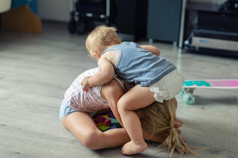 Two little siblings children quarrelling after playing at room at house. Crying offended toddler boy arguing with elder sister. Family rivalry and generation royalty free stock photo