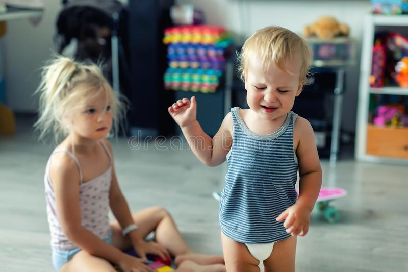 Two little siblings children quarrelling after playing at room at house. Crying offended toddler boy arguing with elder sister. Family rivalry and generation stock images
