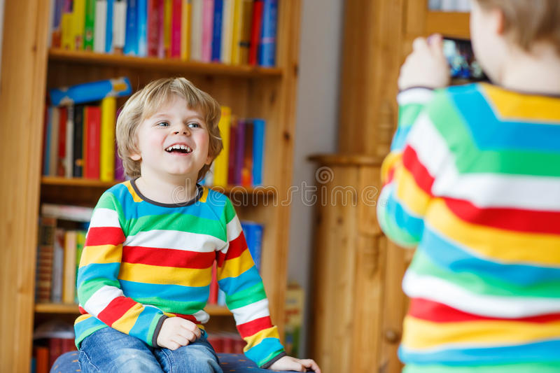 Two little siblings kid boys making photos with photocamera, in. Two funny little kids making photos with photocamera, indoors. Child wearing colorful shirt stock images