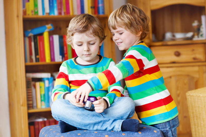 Two little siblings kid boys making photos with photocamera, in. Doors. Children wearing colorful shirt. Lifestyle in a daycare or at home royalty free stock photos