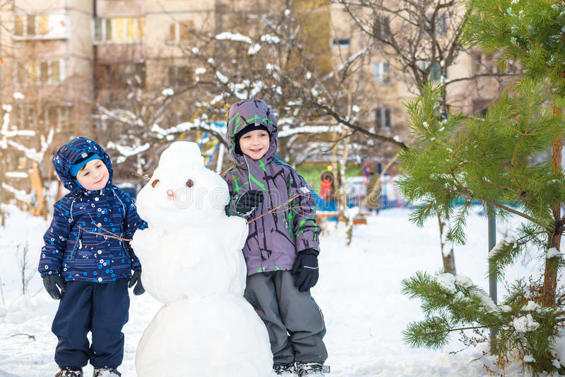 Two little siblings kids boys making a snowman, playing and having fun with snow, outdoors on cold day. Active leisure children in. Winter. happy and smiling stock images