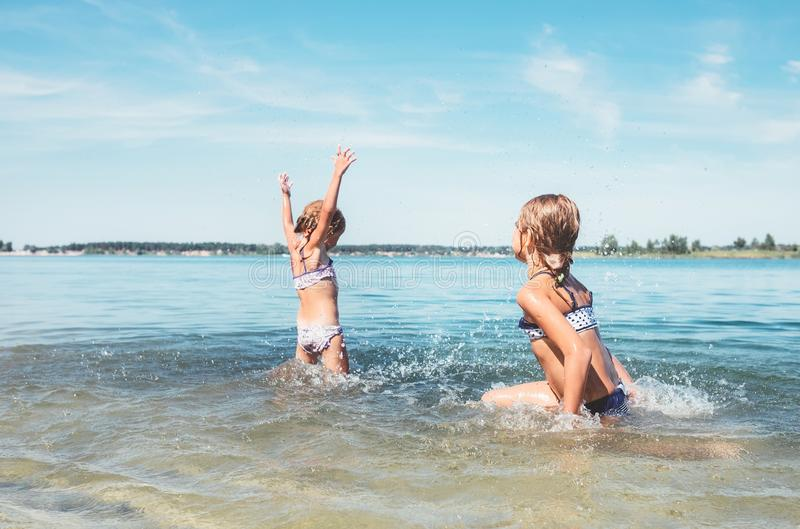 Two little sister girls fooling around in the calm sea waves splashing water to each other. Family vacation concept image royalty free stock photo