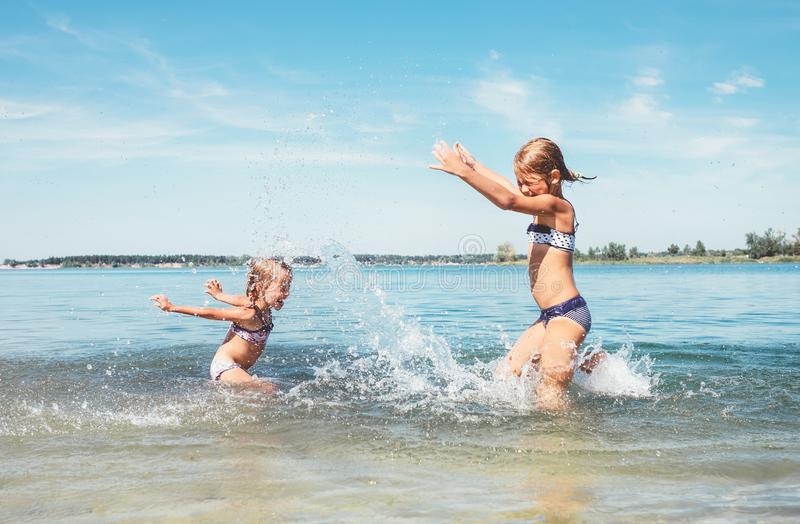 Two little sister girls fooling around in the calm sea waves splashing water to each other. Family vacation concept image stock photography