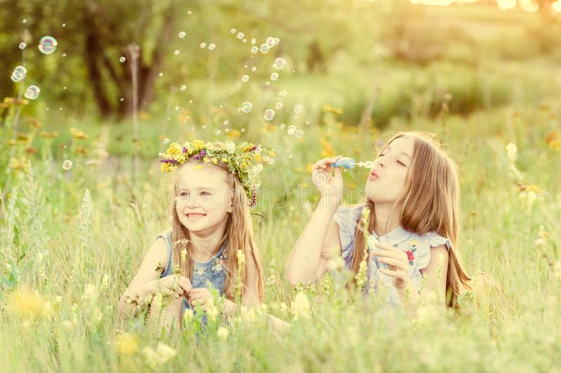Two little sisters blowing soap bubbles stock photography