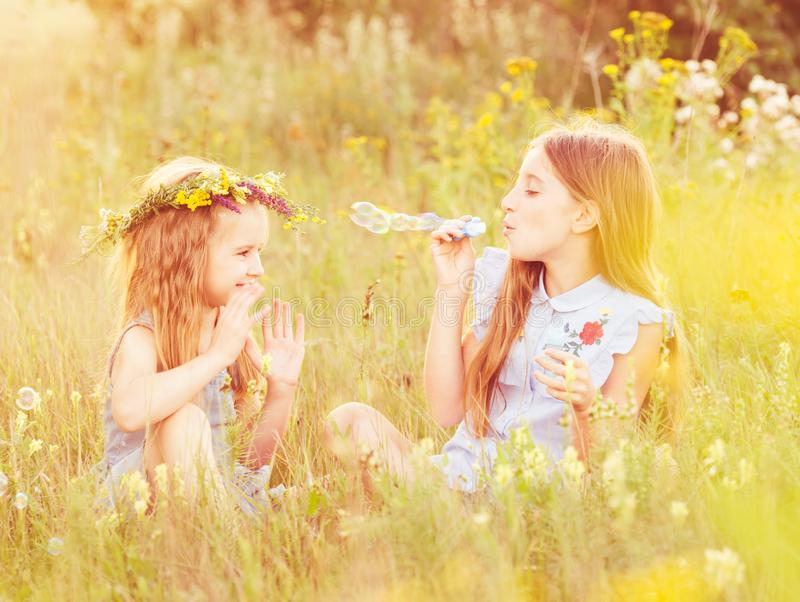 Two little sisters blowing soap bubbles stock photos