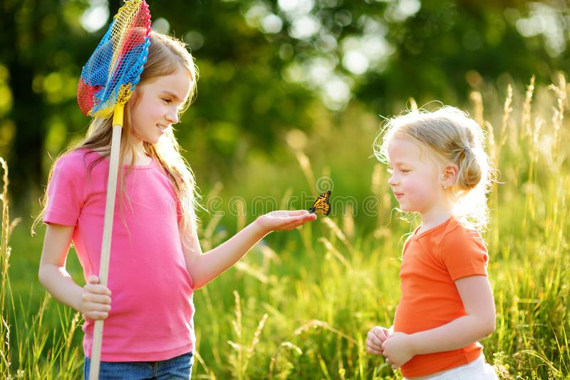 Two little sisters catching butterflies and bugs with their scoop-nets. Kids exploring nature on sunny summer day royalty free stock photography