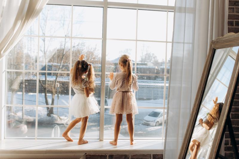 Two little sisters dressed in the beautiful dresses stand on the windowsill next to the mirror.  royalty free stock photo
