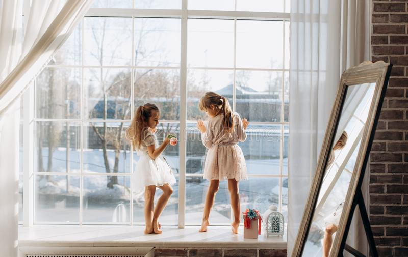 Two little sisters dressed in the beautiful dresses stand on the windowsill next to the mirror  the winter  outside stock image