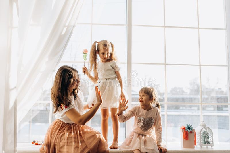 Two little sisters dressed in the beautiful dresses and there young mother sit on the windowsill next to the mirror the royalty free stock photo