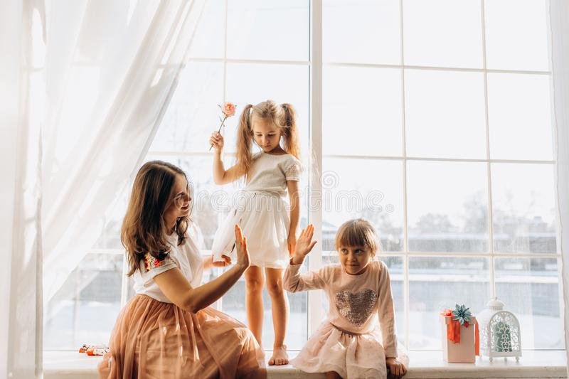 Two little sisters dressed in the beautiful dresses and there young mother sit on the windowsill next to the mirror the stock image
