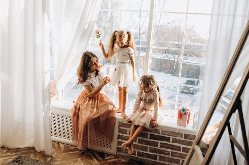 Two little sisters dressed in the beautiful dresses and there young mother sit on the windowsill next to the mirror the stock photos