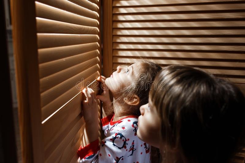 Two little sisters dressed in the pajamas are hiding in the closet with wooden doors stock photos