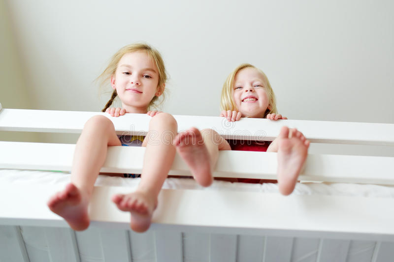 Two little sisters fooling around, playing and having fun in twin bunk bed stock images