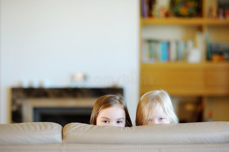Two little sisters having fun at home. Two little sisters playing and laughing at home stock photography