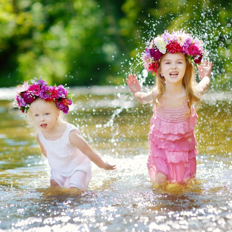 Two little sisters having fun by a river. Two adorable little sisters wearing flowers crowns having fun by a river on warm and sunny summer day royalty free stock photography