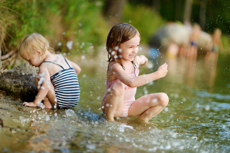 Two little sisters having fun in a river. Two little sisters wearing swimsuits having fun in a river at summer royalty free stock photo