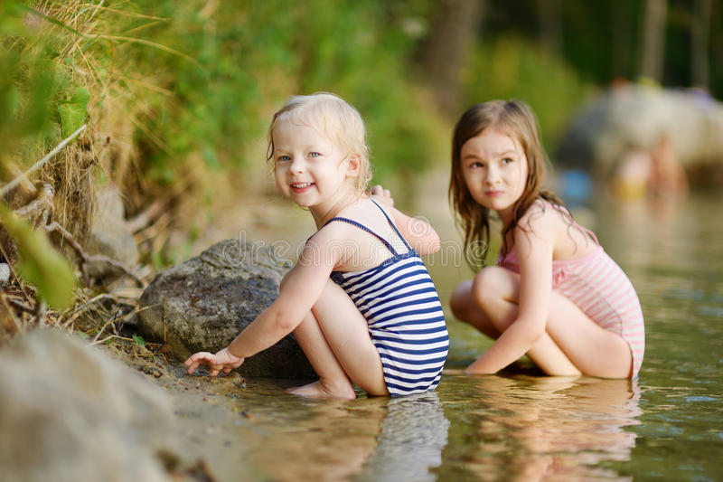 Two little sisters having fun in a river. Two little sisters wearing swimsuits having fun in a river at summer royalty free stock photos