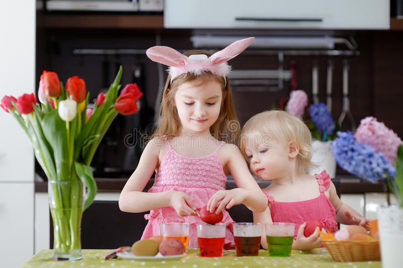 Two little sisters painting Easter eggs stock photo