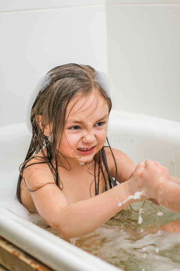Two little sisters play in a bath. royalty free stock photos
