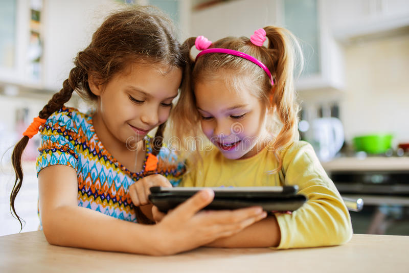 Two little sisters play on a Tablet PC stock images