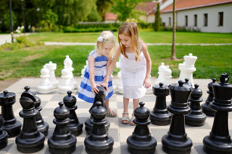 Two little sisters playing giant chess stock photos