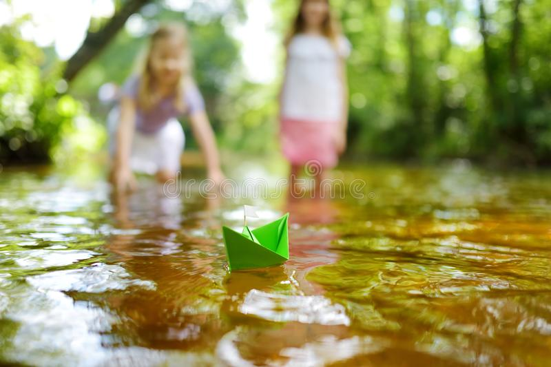 Two little sisters playing with paper boats by a river on warm and sunny summer day. Children having fun by the water. Summer activities for small kids royalty free stock image