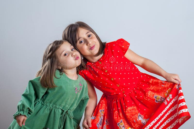 Two little sisters posing for the camera in the studio royalty free stock photos