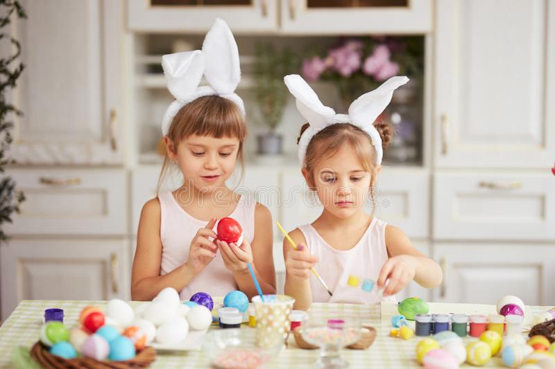 Two little sisters with white rabbit`s ears on their heads dye the eggs for the Easter table in the cozy light kitchen stock photo