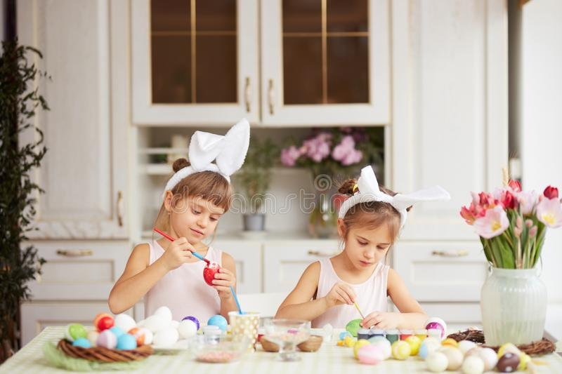Two little sisters with white rabbit`s ears on their heads dye the eggs for the Easter table in the cozy light kitchen stock image