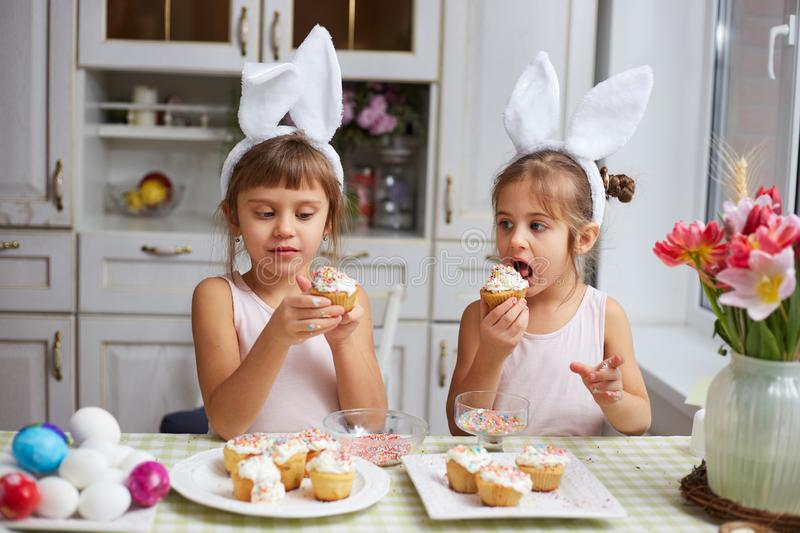 Two little sisters with white rabbit`s ears on their heads eat small Easter cakes in the cozy light kitchen stock photo