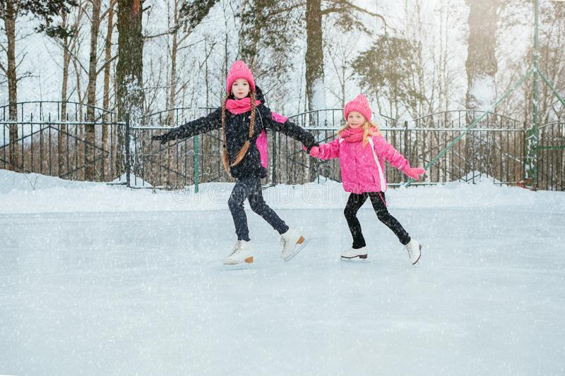 Two Little smiling girls skating on ice in pink wear and hand made scarfs. Outdoor. Winter stock photos