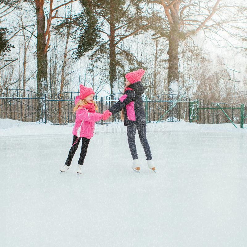 Two Little smiling girls skating on ice in pink wear and hand made scarfs. Outdoor. Winter stock photography